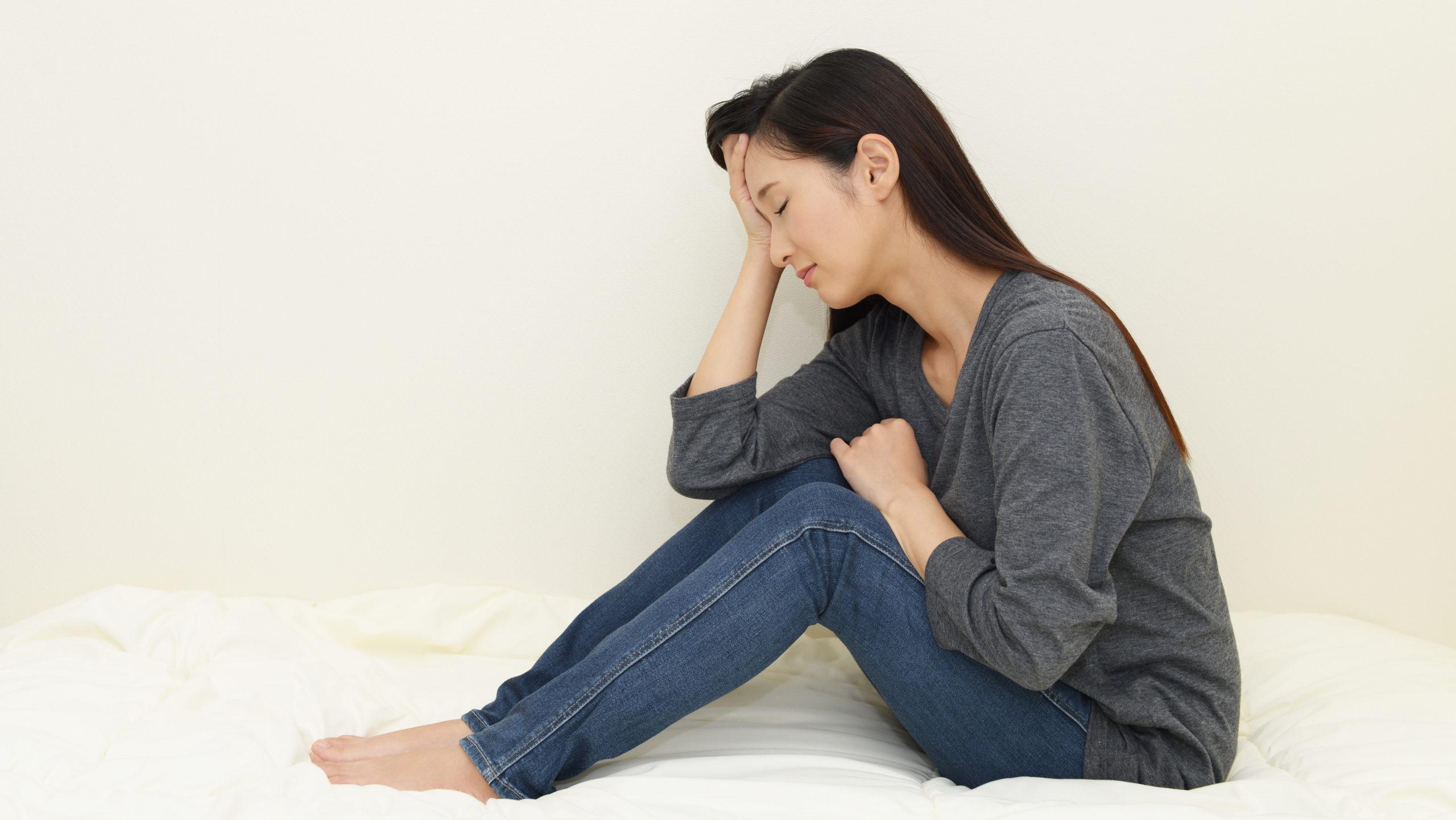 床に座り悩む女性